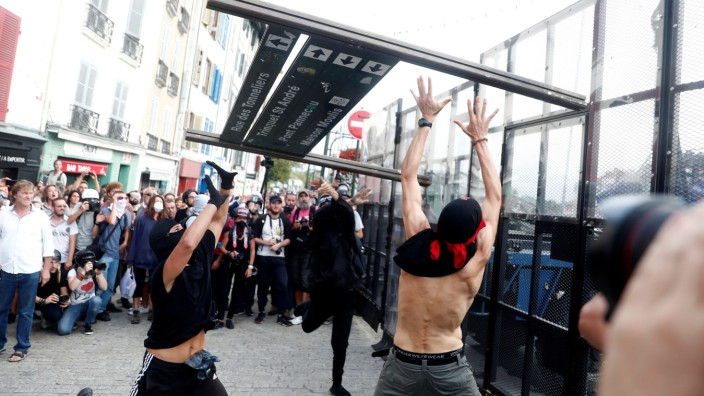 Demonstrators use a part of a barricade to attack the police blockade during a protest against G7 summit, in Bayonne