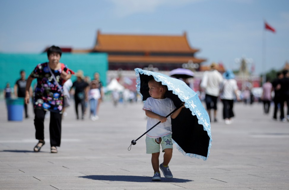 A boy holds an umbrella on Tiananmen Square in Beijing