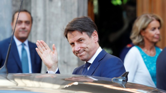 Italian Prime Minister Giuseppe Conte waves as he leaves the Senate in Rome