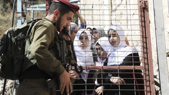 Nahostkonflikt: Palästinensische Schüler und ein israelischer Soldat in Hebron. Die Stadt im Westjordanland ist ein Schauplatz des Nahostkonflikts.
