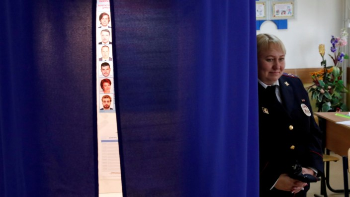 FILE PHOTO: A police officer stands guard near a voting booth at a polling station during the Moscow city parliament election in Moscow