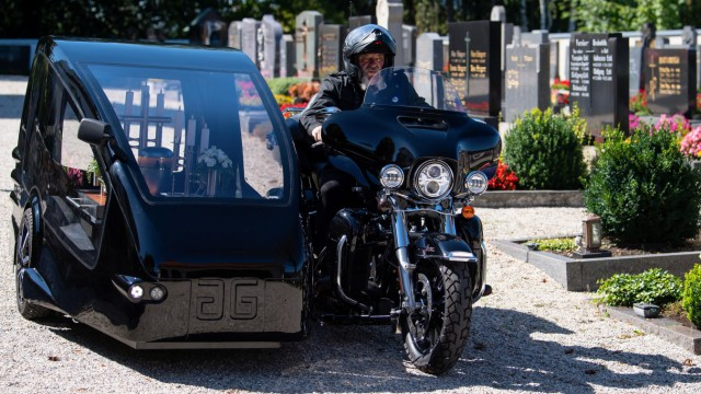 Bestatter Wolfgang Frisch fährt mit seinem Bestattungsmotorrad, einer umgebauten Harley-Davidson, über einen Friedhof.
