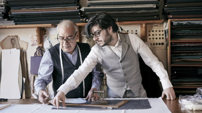 A tailor and a younger man, an assistant or apprentice working together, measuring cloth and cutting patterns.
