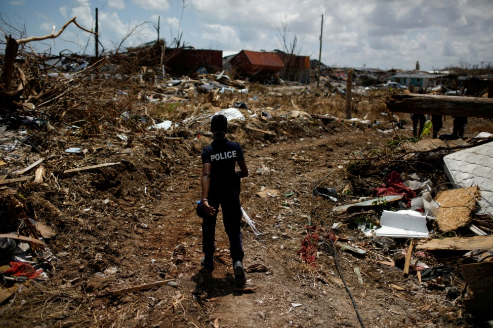 FILE PHOTO: A police officer searches for the dead in the destroyed Mudd neighborhood after Hurricane Dorian hit the Abaco Islands in Marsh Harbour
