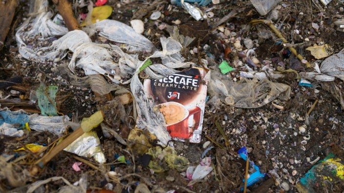 A sachet of Nestle's Nescafe coffee is pictured amidst a garbage-filled shore in Freedom Island, Paranaque City