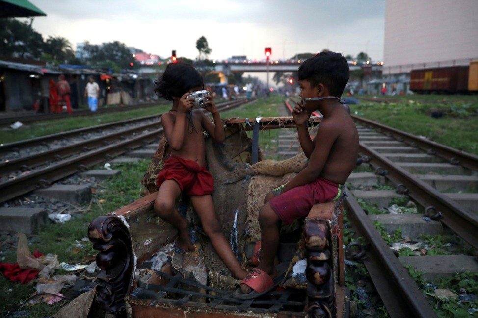 Children act out taking pictures with a non-functioning camera in Dhaka