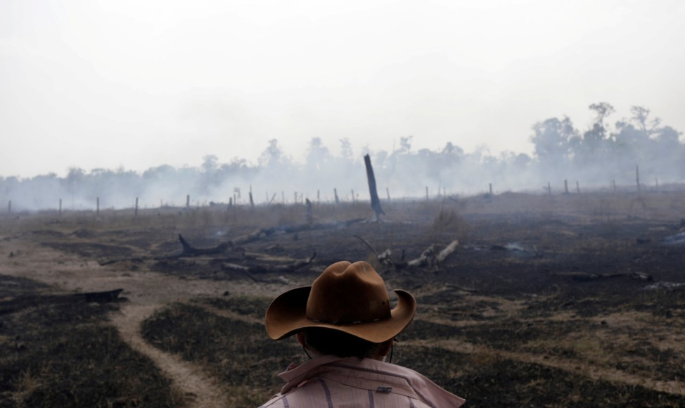 Avaci, 77, who is an employee of a farm, walks on a smoldering field after it was hit by a fire burning a tract of the Amazon forest as it is cleared by farmers, in Rio Pardo