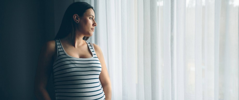 A young pregnant woman looking out of the window creative PUBLICATIONxINxGERxSUIxAUTxONLY Copyrigh