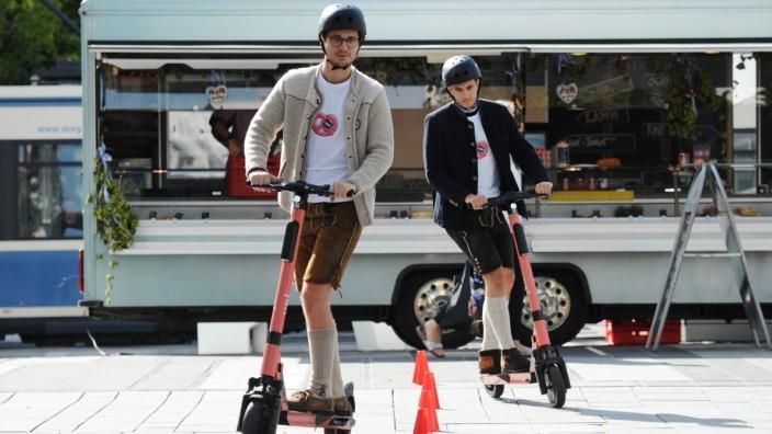 Zwei Männer absolvieren einen kleinen Parcours mit E-Rollern.