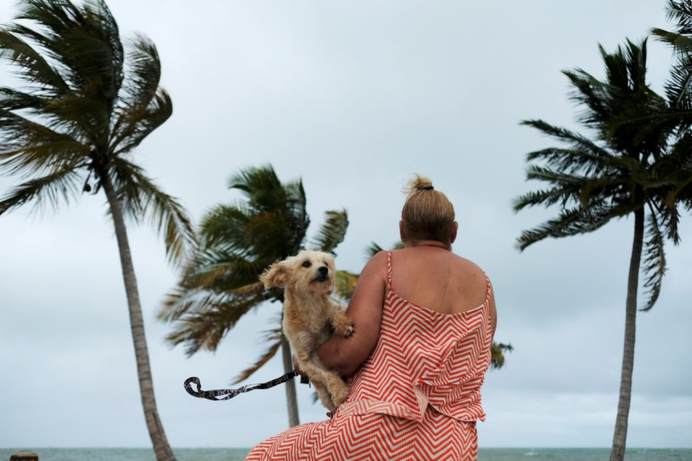 A woman holds her dog as she surveys the water as Tropical Storm Karen approaches in Yabucoa
