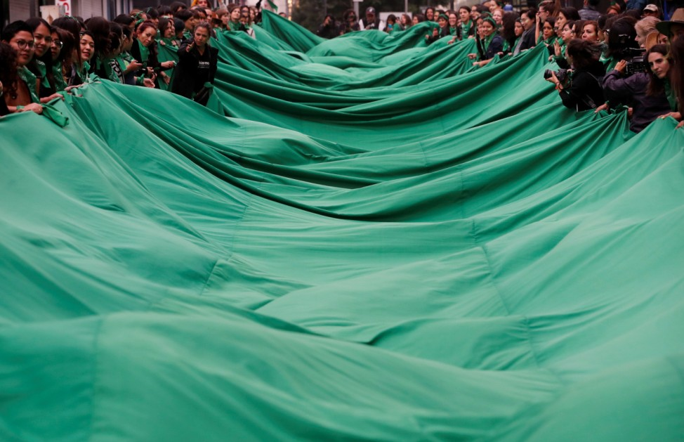 Activists, part of a movement known as 'Marea Verde' take part in a performance to film a message to spread awareness during the International Safe Abortion Day in Mexico City