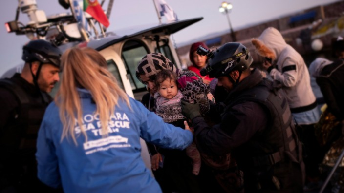 A migrant holding a baby is helped to disembark a Frontex patrol vessel carrying migrants rescued at open sea, at the port of Skala Sikamias