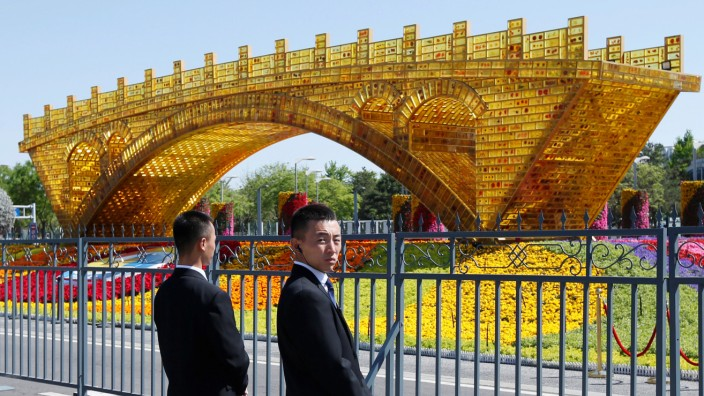 Security personnel stand guard near a 'Golden Bridge on Silk Road' decoration for the Belt and Road Forum outside the China National Convention Center in Beijing, China