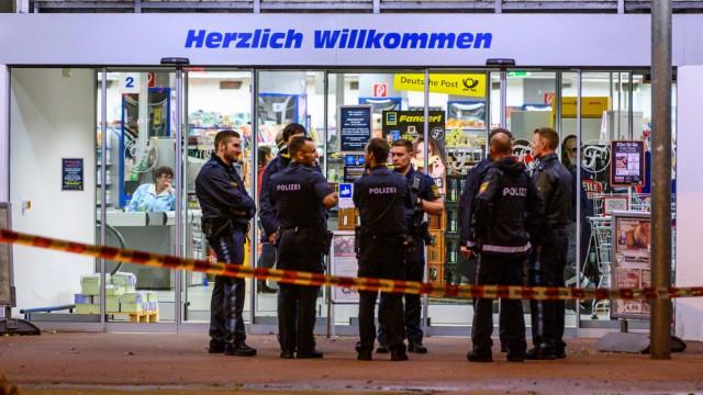 Einsatzkräfte der Polizei stehen auf einem Parkplatz neben einem Supermarkt, vor dem Schüsse gefallen sind.