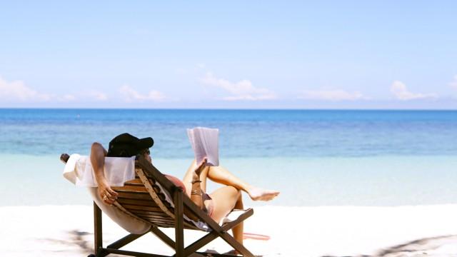 Eine Urlauberin liegt im Liegestuhl am Strand.