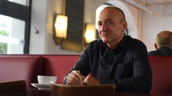 Rainer Jund war Arzt am Klinikum Großhadern und hat nun ein Buch geschrieben, er sitzt an einem Tisch im Cafe.