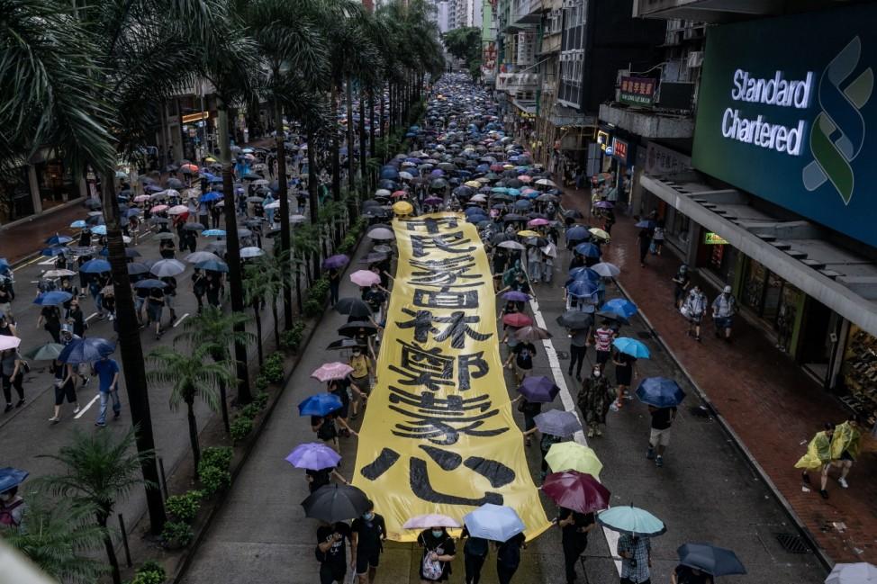 Schutzschirme: Zehntausende demonstrieren im chinesischen Hongkong gegen das Vermummungsverbot.