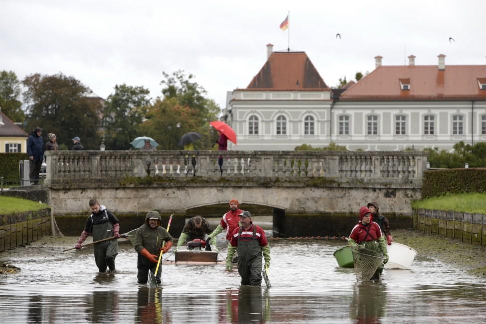 Ganz in grün und mit großen Keschern sind die Fischer ins Wasser des Nymphenburger Kanals im Schlosspark Nymphenburg gestiegen, um die Fische aus dem Wasser zu ziehen.