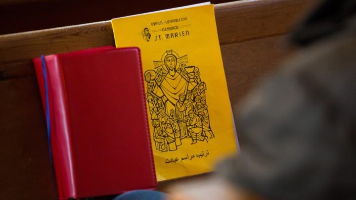 Kirche: Christliche Broschüre auf arabisch auf einer Kirchenbank