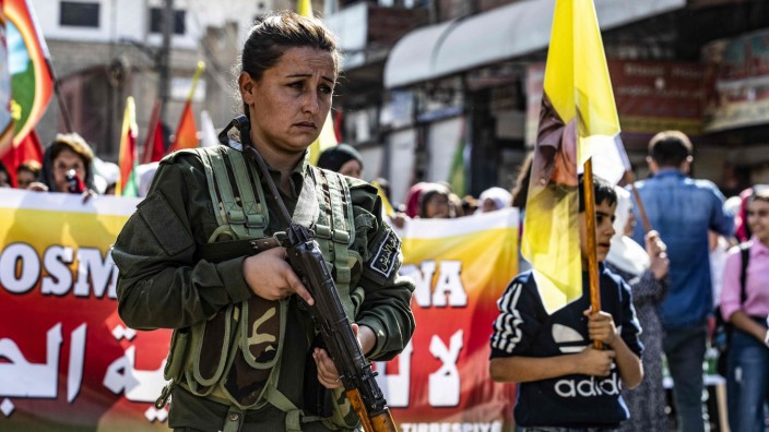 Syrien: Eine kurdische Polizistin begleitet einen Demonstrationszug in Al-Qahtaniyya