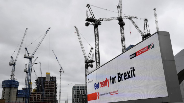 FILE PHOTO: An electronic billboard displaying a British government Brexit information awareness campaign advertisement is seen near construction cranes in London, Britain