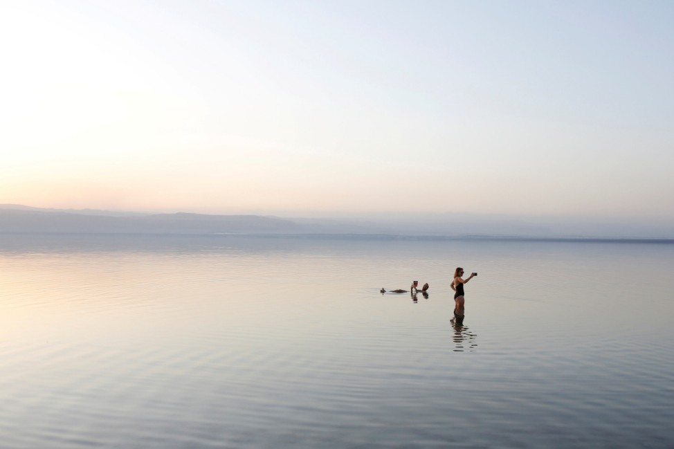 People take a swim on the shores of the Dead Sea near Amman