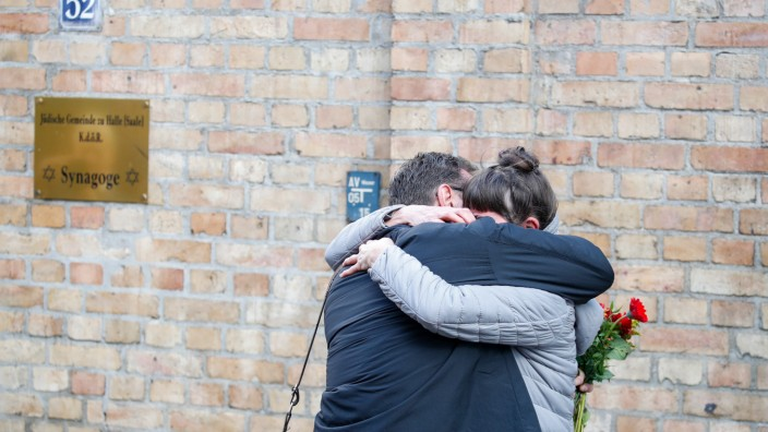Zwei Menschen trauern nach dem rechtsradikalen Anschlag in Halle an der Saale