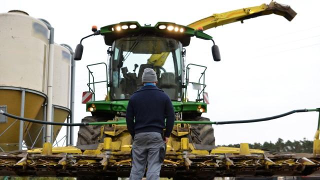 Ein Bauer steht vor seinem Maishäcksler.