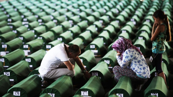A Bosnian Muslim family cries near the coffin of a relative, which was prepared for a mass burial at the Memorial Center in Potocari, near Srebrenica