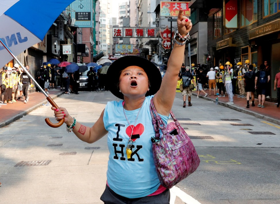 An anti-government demonstrator shouts toward Tsim Sha Tsui Police Station during a protest in Hong Kong