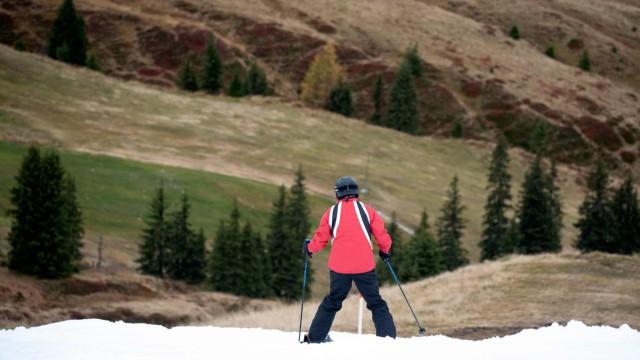 Saisonstart in Kitzbühel: Wanderer und Mountainbiker sind noch in kurzärmeligen Funktionsklamotten unterwegs, die ersten Wintersportler aber fahren in voller Montur das weiße Band hinab.