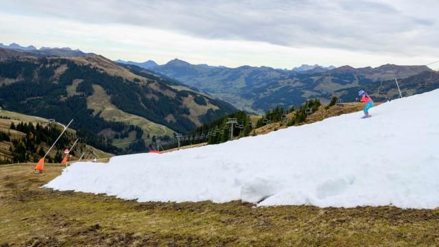 Saisonstart in Kitzbühel: Wie lange diese Piste inmitten schneefreier Gipfel hält, hängt vom Wetter ab.