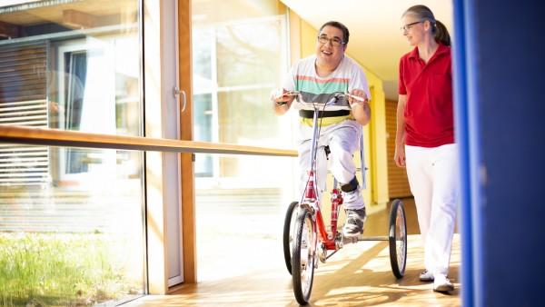 """Ein Mann fährt im Verein """"Helfende Hände"""" auf einem Dreirad."""