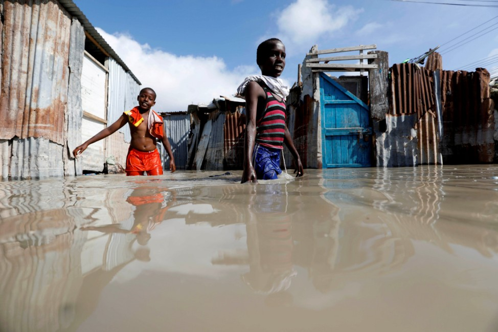 Somali children wade through flood waters after heavy rain in Mogadishu