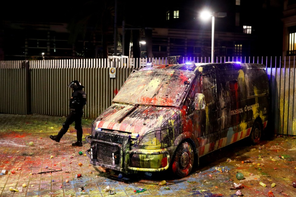 A police officer kicks a balloon next to a van that was covered with paint during a protest outside the Spanish government delegation offices in Barcelona