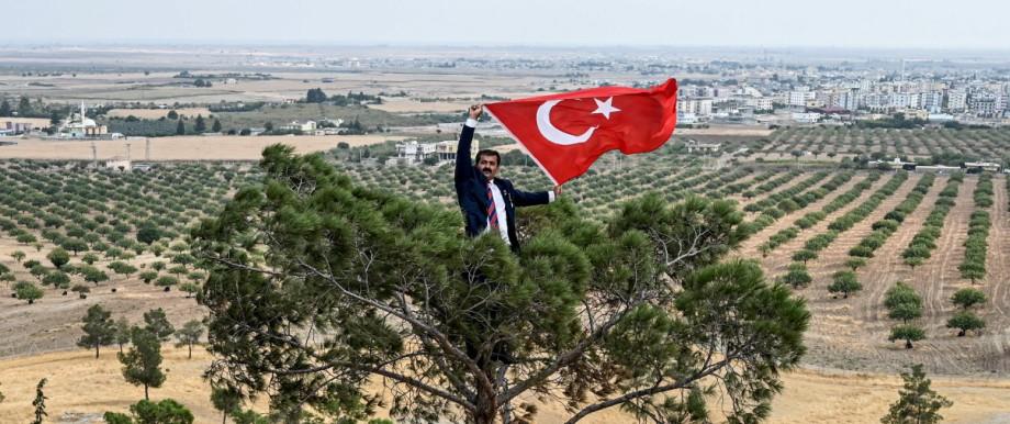 Türkei: Ein Mann hält an der Grenze zu Syrien eine türkische Flagge hoch