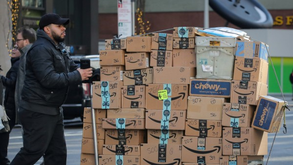 FILE PHOTO: A delivery person pushes a cart full of Amazon boxes in New York