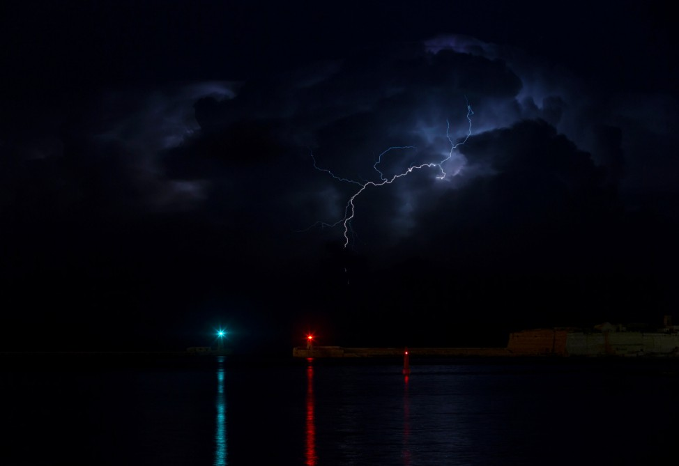A lightning storm is seen beyond the entrance to Valletta's Grand Harbour