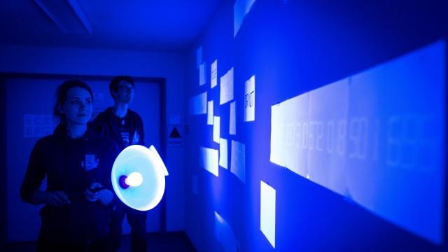 TU Garching: Katharina Schaar und Benedict Dingfelder zeigen einen Raum mit Codes, die nur im Schwarzlicht zu entziffern sind.