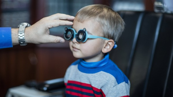 Boy doing eye test at optometrist model released Symbolfoto property released PUBLICATIONxINxGERxSUI