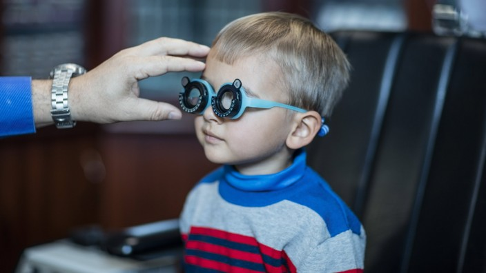 Boy doing eye test at optometrist model released Symbolfoto property released PUBLICATIONxINxGERxSUI