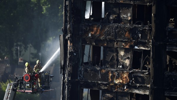 FILE PHOTO: Firefighters spray water onto the Grenfell Tower block which was destroyed in a disastrous fire, in north Kensington, West London