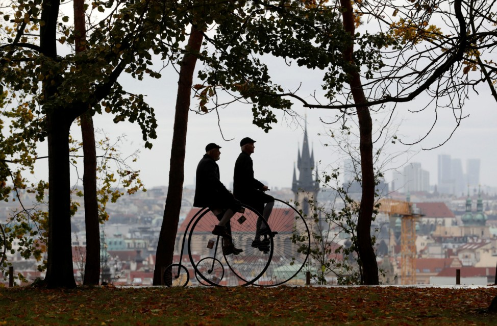 Participants wearing historical costumes ride their high-wheel bicycles in Prague