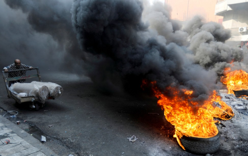 Iraqi demonstrators burn tires as they block the road during ongoing anti-government protests, in Baghdad