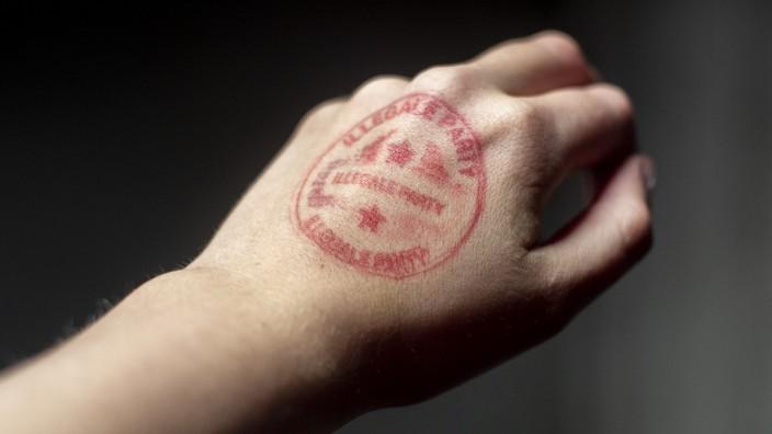 """Eine Hand mit einem Stempelaufdruck: """"Illegale Party""""."""