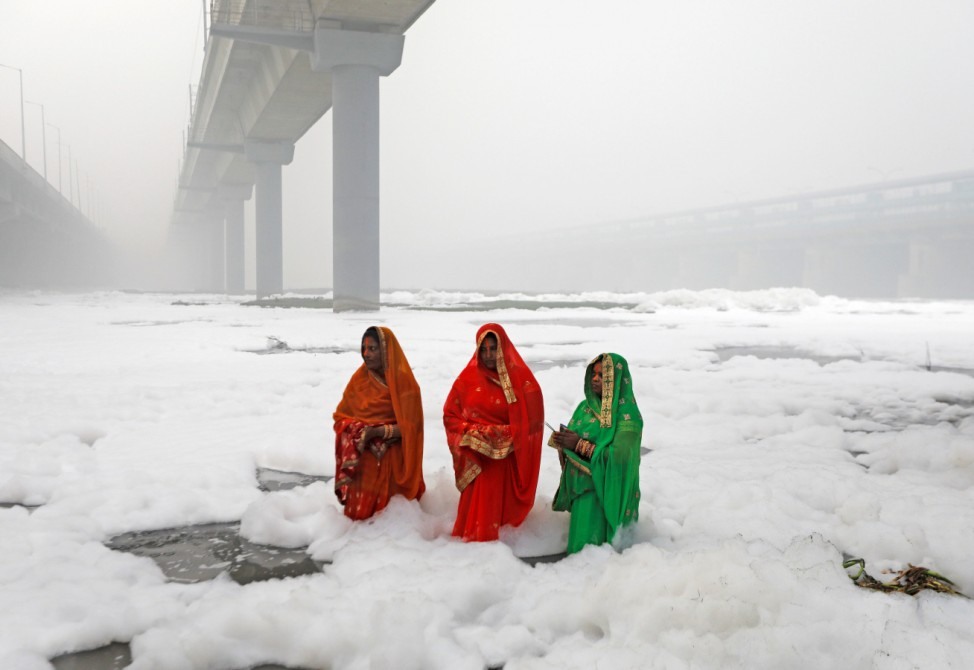 Hindu women worship the Sun god in the polluted waters of the river Yamuna during the Hindu religious festival of Chatth Puja in New Delhi