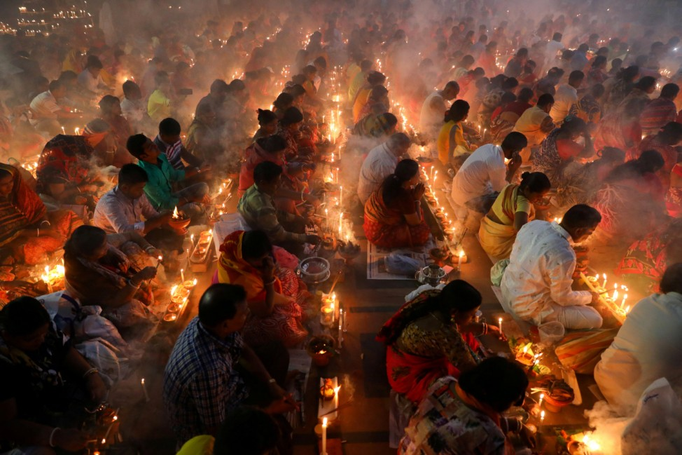 Hindu devotees sit together on the floor of a temple to observe Rakher Upabash, in Narayangonj