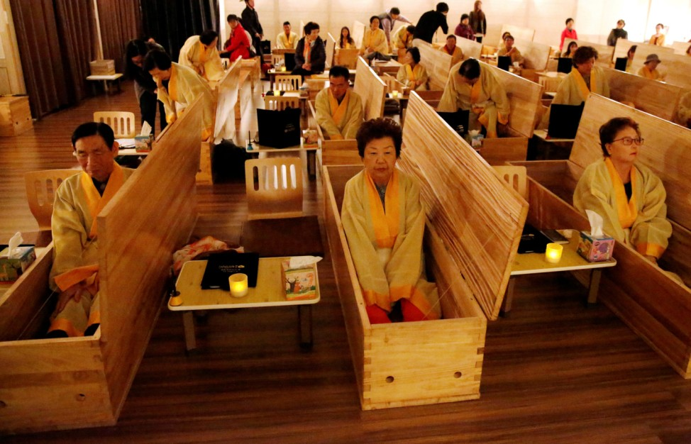 Participants sit inside coffins during a 'living funeral' event as part of a 'dying well' programme, in Seoul, South Korea
