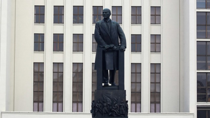 People lay flowers at a monument of the Soviet state founder Vladimir Lenin in Minsk
