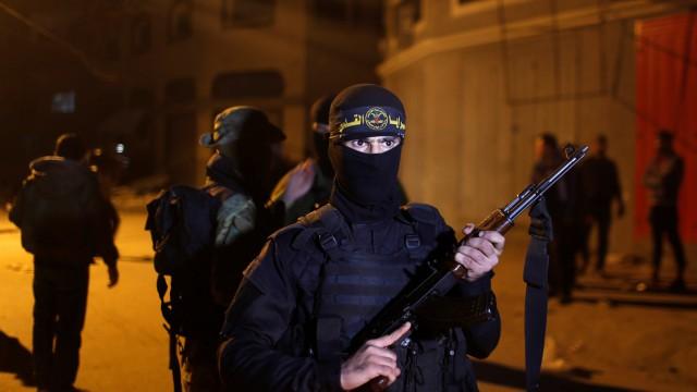 Palestinian Islamic Jihad militant stands guard at the scene of an Israeli strike that killed the group's field commander Baha Abu Al-Atta in Gaza City